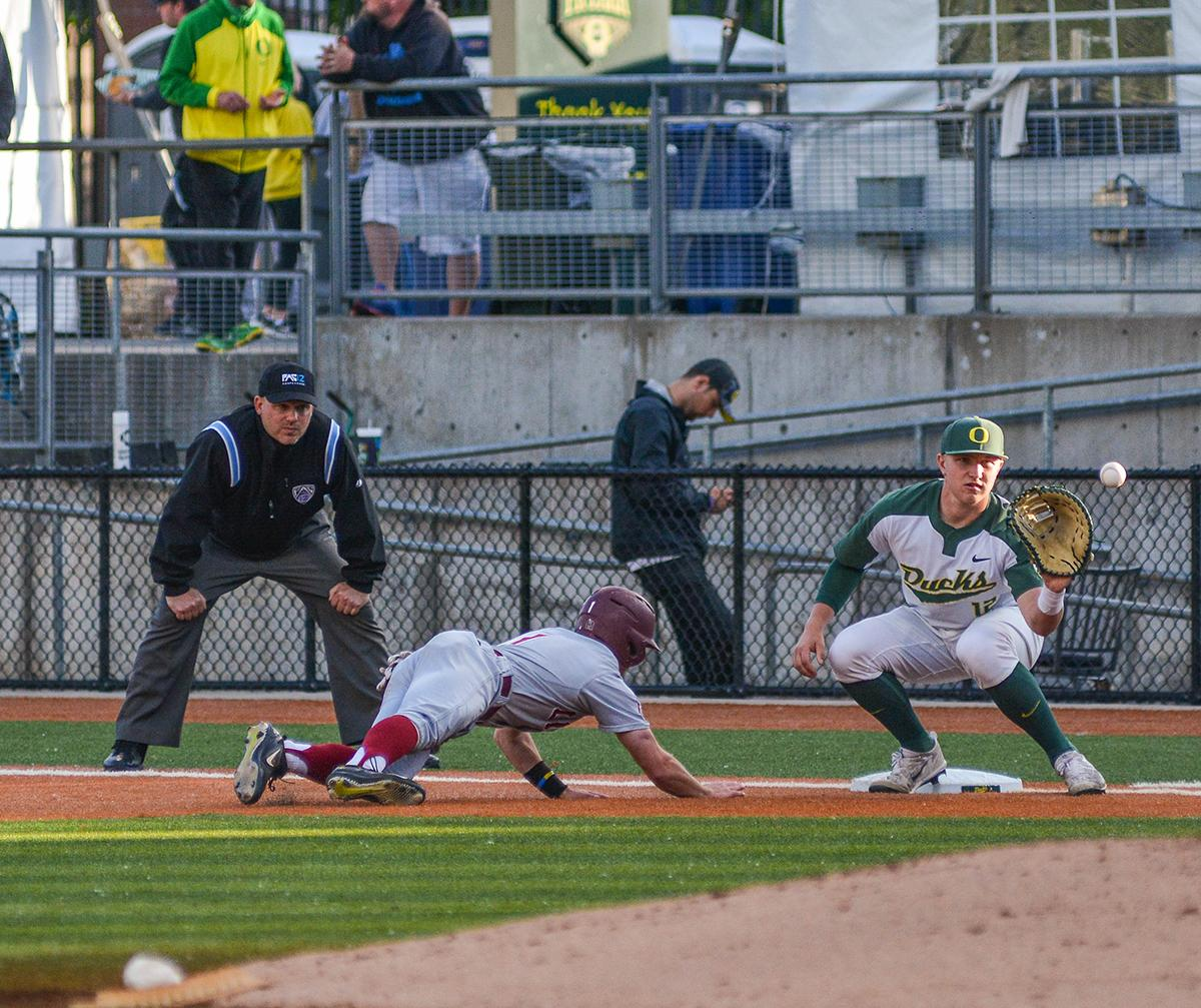 Ducks first baseman Gabe Mathews (#12) catches the ball as Lions runner Phil Caulfield (#1) slides back into the bag. On Wednesday night the Ducks fell to the Loyola Marymount Lions 4-0 at PK Park. Photo by Jacob Smith, Oregon News Lab
