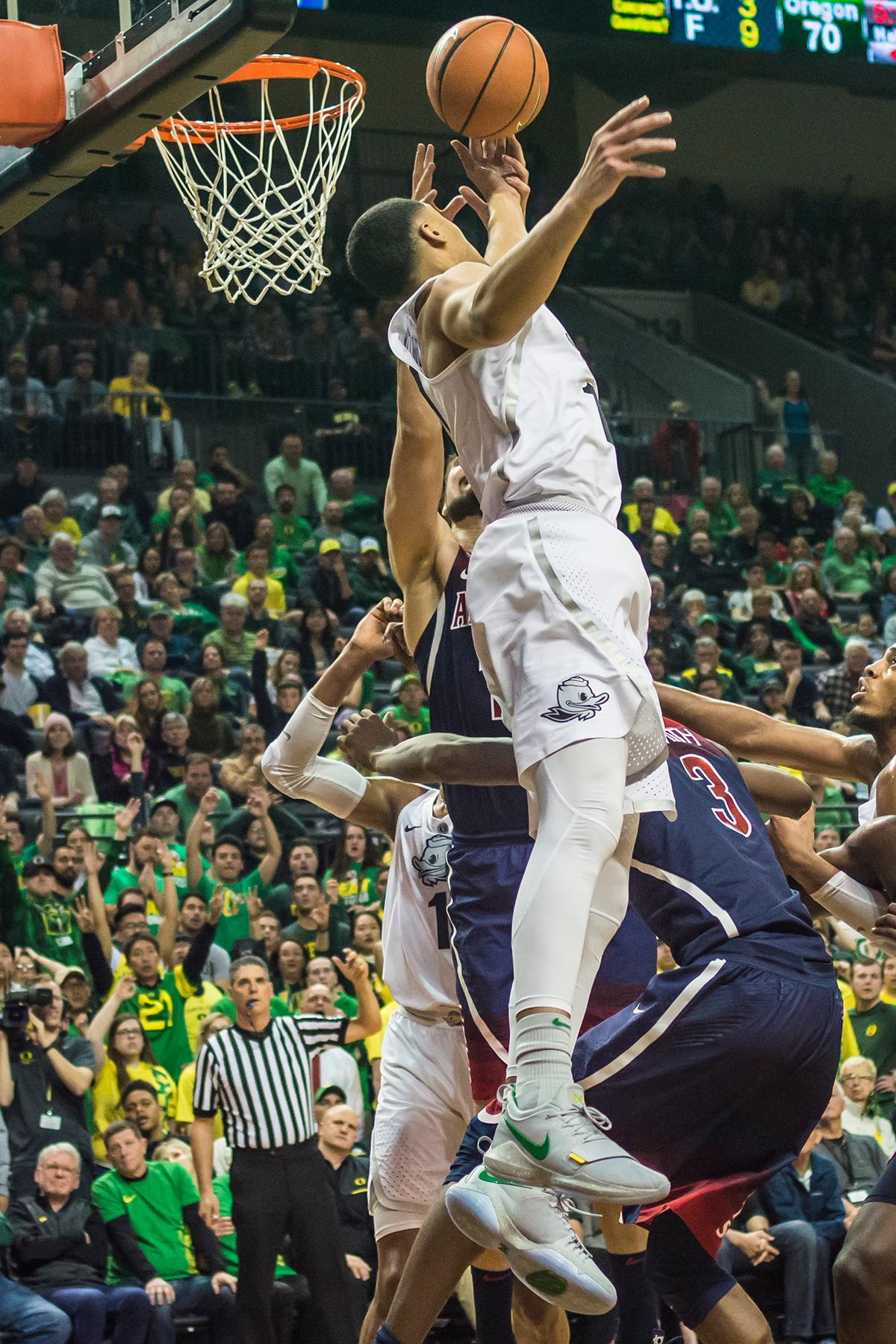 Oregon's Keith Smith goes for a layup against Arizona defenders in their matchup at Matthew Knight Arean Saturday. The Ducks upset the fourteenth ranked Wildcats 98-93 in a stunning overtime win in front of a packed house of over 12,000 fans for their final home game to improve to a 19-10 (9-7 PAC-12) record on the season. Oregon will finish out regular season play on the road in Washington next week against Washington State on Thursday, then Washington on the following Saturday. (Photo by Colin Houck)