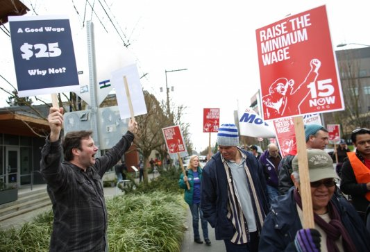 Activists march while a contrarian opposes Seattle's controversial $15 minimum wage law.{ }