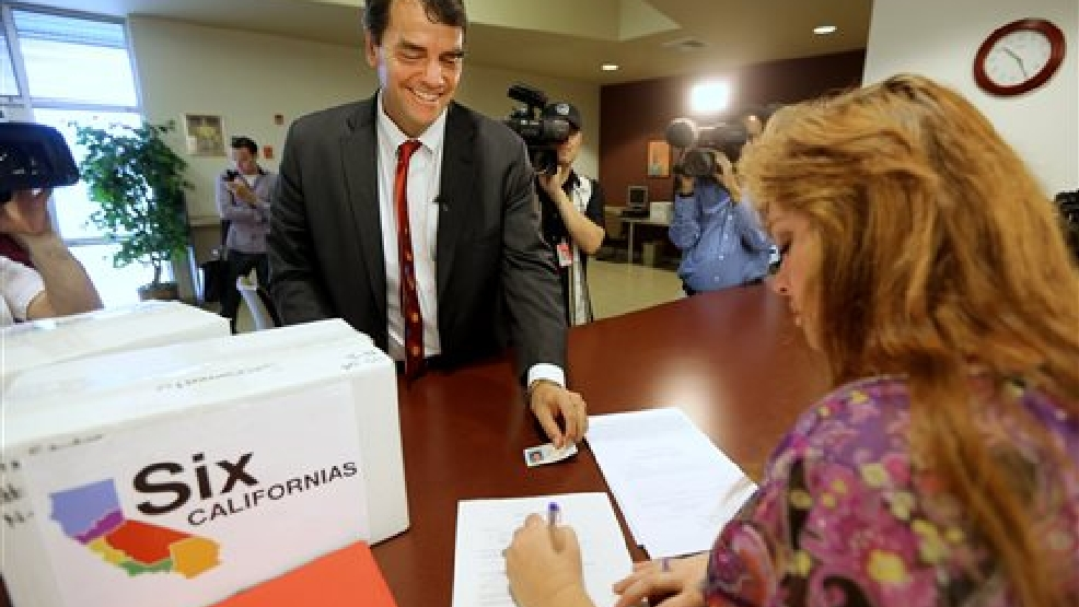 Silicon Valley venture capitalist Tim Draper presents his drivers license for identification purposes to Heather Ditty, elections manager for the Sacramento County Registrar of Voters, as he turns in boxes of petitions for a ballot initiative that would ask voters to split California into six separate states, Tuesday, July 15, 2014, in Sacramento, Calif. Draper delivered what he said were 44,000 signatures, of the 1.3 million the Six California's campaign plans to submit statewide this week. If enough signatures are verified, voters in November 2016 would be asked to divide the state into six states called Jefferson, North California, Silicon Valley, Central California, West California and South California. (AP Photo/Rich Pedroncelli)