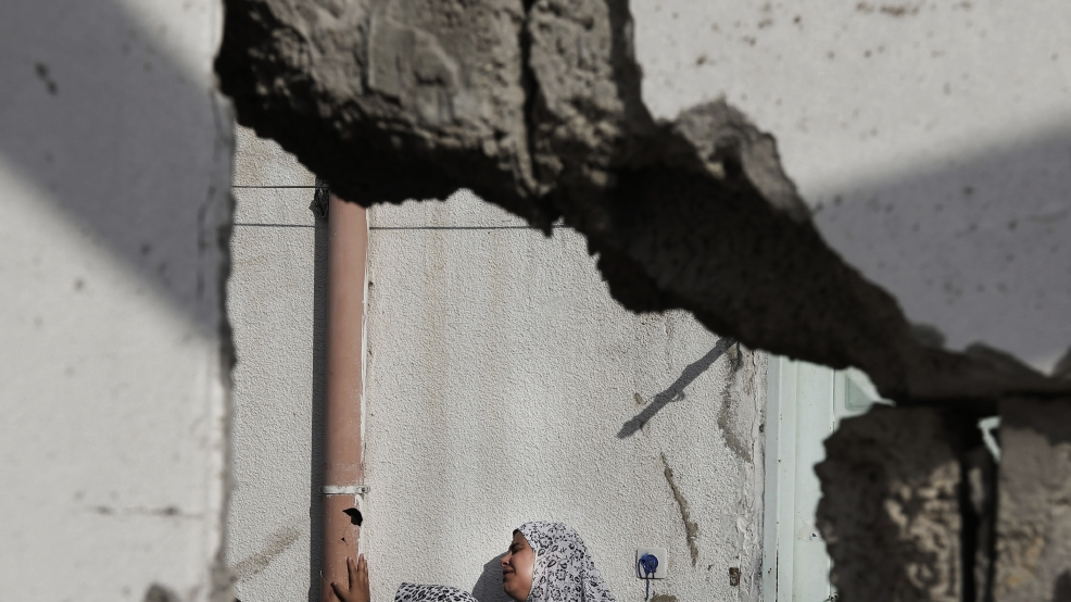 A Palestinian relative of the Abu Wahdan family cries outside a damaged house in the Jebaliya refugee camp that was hit by an Israeli strike that killed several members of the family, in the northern Gaza Strip, Sunday, Aug. 3, 2014. Jamila, 55, Hatem, 57, and Sanwara Abu Wahdan, 27, were killed at the house after the extended family of more than 40 people had sought refuge in Jebaliya from shelling elsewhere. (AP Photo/Lefteris Pitarakis)