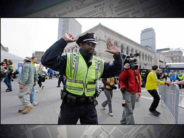 Boston police officer clears Boylston Street following explosions at the finish line of the 2013 Boston Marathon.