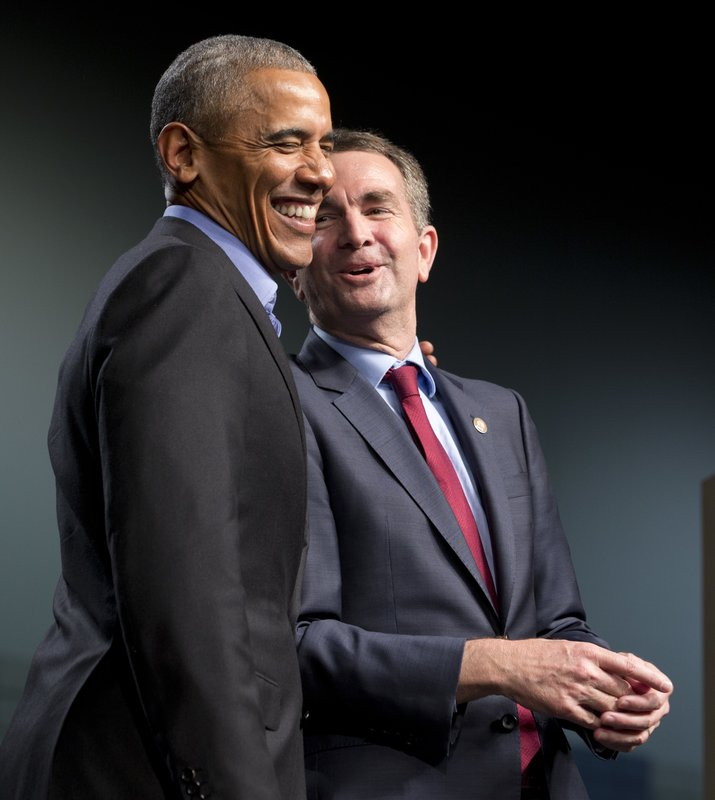 FILE - This Thursday Oct. 19, 2017 file photo shows former President Barack Obama, left, as he shares a laugh with Democratic gubernatorial candidate Lt. Gov., Ralph Northam, during a rally in Richmond, Va. Northam may have a politician's dream background, but he's still struggling with how to define himself in the age of Trump. (AP Photo/Steve Helber)<p></p>