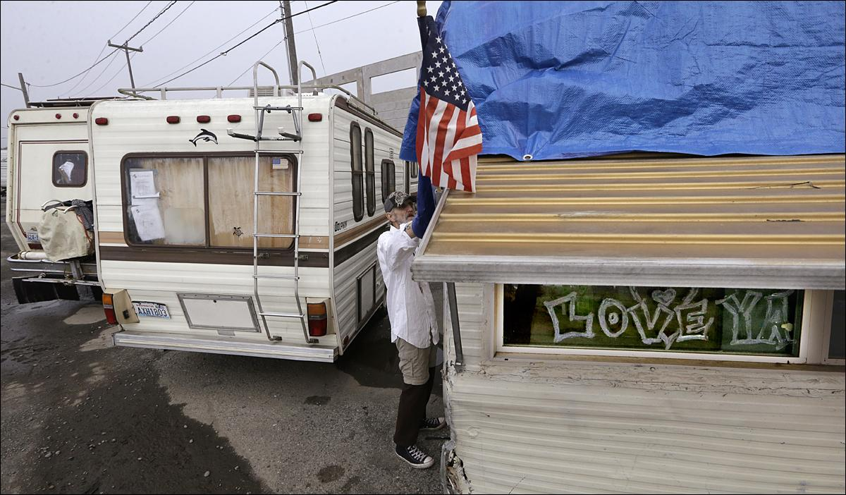seattle in uncharted territory as homelessness spikes komo dennis berg secures a tarp over his 28 foot trailer parked in a temporary city