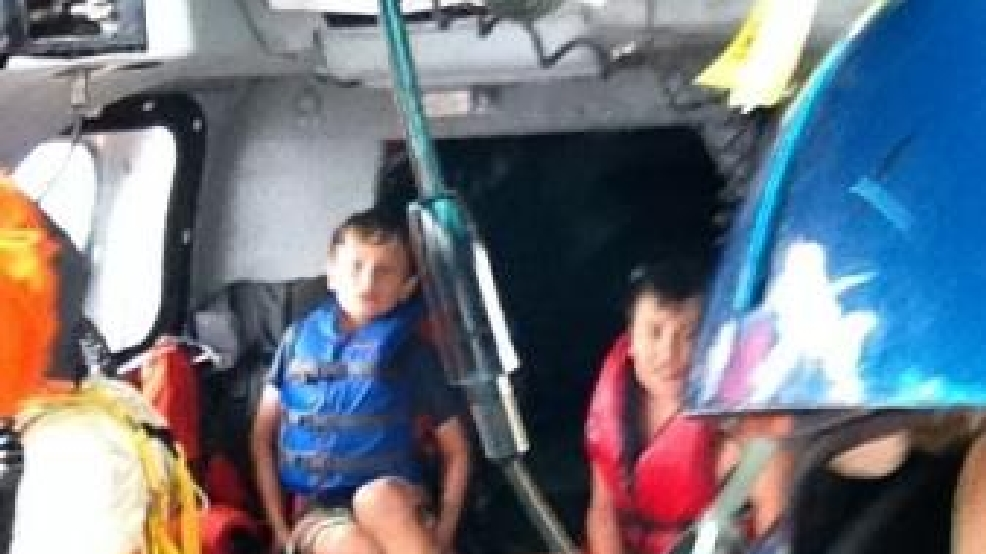 Thomas Alter and Zachary Suri sit aboard a Coast Guard Dolphin helicopter from Air Station Traverse City, Mich., after being rescued July 11, 2014. The boys, along with Suri's mother, were rescued from Whaleback Shoal in Green Bay after being stranded on the water overnight when their kayaks went adrift. U.S. Coast Guard photo by Cmdr. Shad Soldano