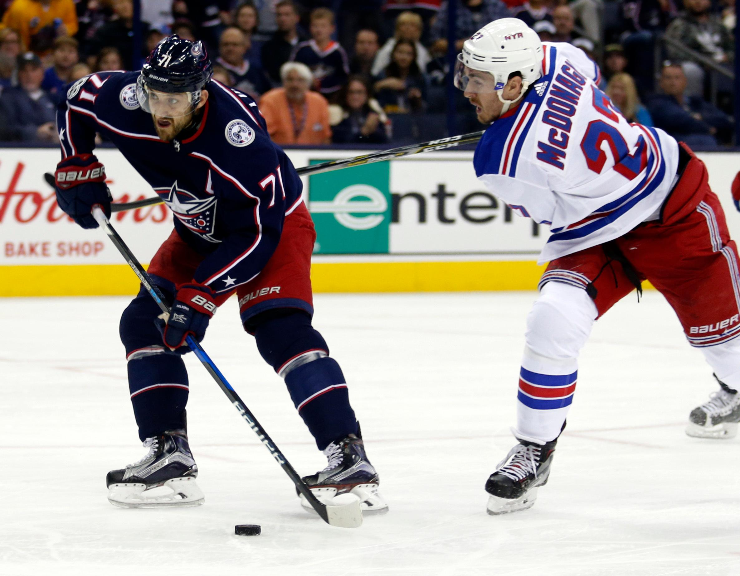 Columbus Blue Jackets forward Nick Foligno, left, tries to shoot the puck against New York Rangers defenseman Ryan McDonagh during the second period of an NHL hockey game in Columbus, Ohio, Friday, Oct. 13, 2017. McDonagh was called for slashing on the play.(AP Photo/Paul Vernon)