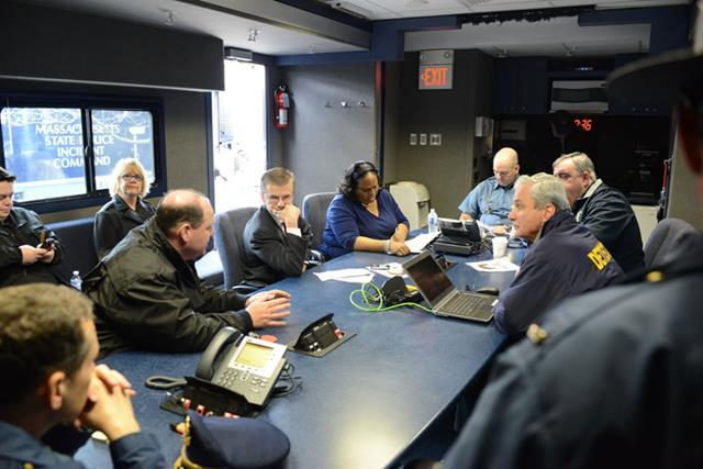 Federal, state, and local officials strategize in mobile state police command post