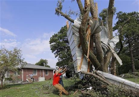Residents try to free a house panel from where it was lodged against a tree following a tornado in Bennet, Neb., Friday.