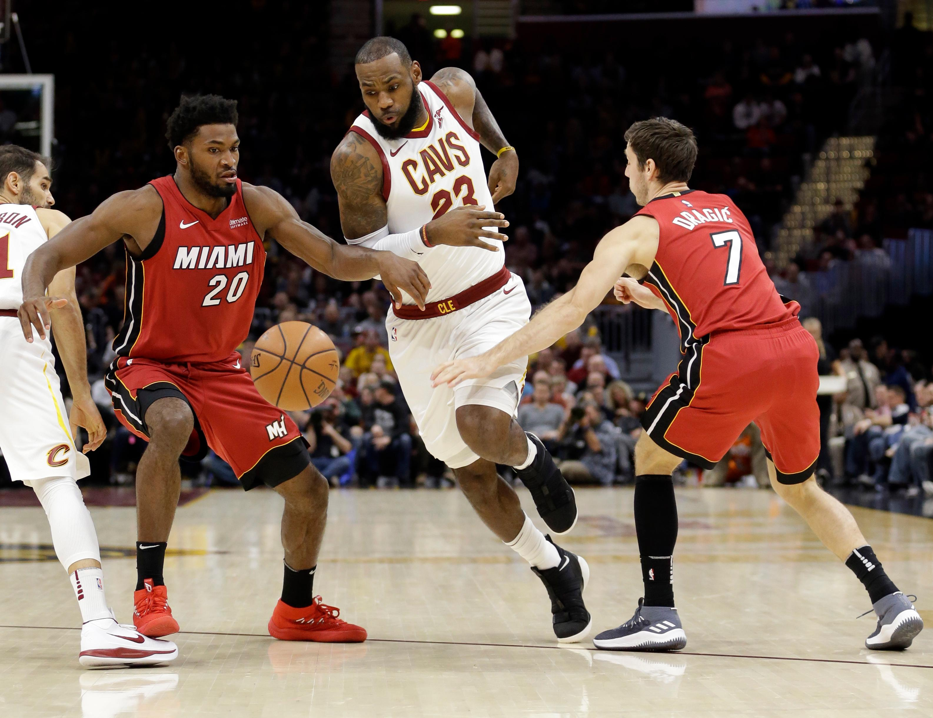 Cleveland Cavaliers' LeBron James (23) drives between Miami Heat's Justise Winslow (20) and Goran Dragic, from Slovenia, in the first half of an NBA basketball game, Tuesday, Nov. 28, 2017, in Cleveland. (AP Photo/Tony Dejak)