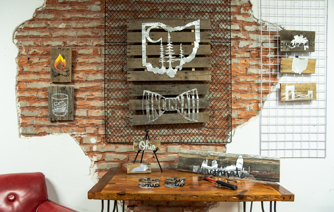 Sara Cole of Sara Cole Art Designs creates rustic wall hangings using reclaimed pallet and barn wood with detailed cut aluminum. Her work pays homage to the region and its charms, such as the Roebling bridge, Kentucky bourbon, and the great outdoors. / Image: Melissa Sliney // Published: 6.26.19<br>