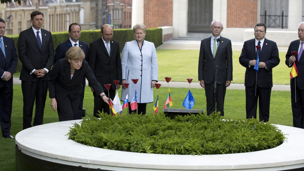 German Chancellor Angela Merkel, third left, places a porcelain poppy during the inauguration of a Peace Bench at the Menin Gate in Ypres, Belgium on Thursday, June 26, 2014. Where their countrymen once slaughtered each other with machine guns, artillery and poison gas, the leaders of Britain, Germany and the other member states of the European Union gathered Thursday to solemnly mark the 100th anniversary of the start of World War I and rededicate themselves to peace and working together. Other heads of state from left, European Union heads of state, from left, Cypriot President Nicos Anastasiades , Slovenian President Borut Pahor, French President Francois Hollande, Romanian President Traian Basescu, Lithuanian President Dalia Grybauskaite, European Council President Herman Van Rompuy and European Commission President Jose Manuel Barroso. (AP Photo/Virginia Mayo)
