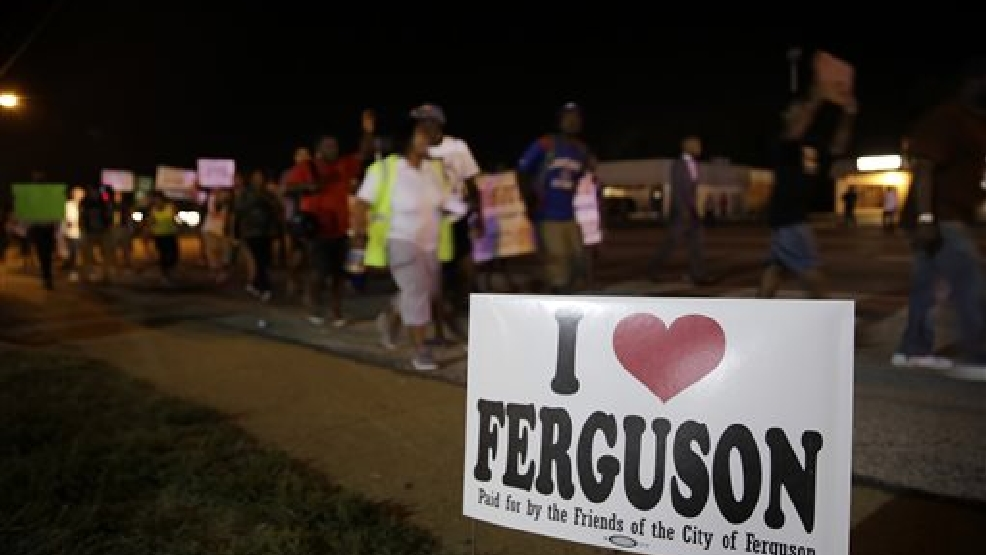 Protesters march Thursday, Aug. 21, 2014, in Ferguson, Mo. Protesters again gathered Thursday evening, walking in laps near the spot where Michael Brown was shot. Some were in organized groups, such as clergy members. More signs reflected calls by protesters to remove the prosecutor from the case. (AP Photo/Jeff Roberson)