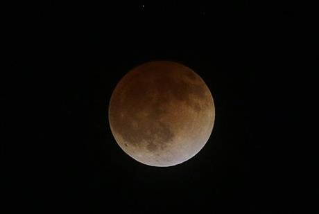 This photo shows the Earth's shadow cast over the surface of the moon as a total lunar eclipse over the Chabot Space and Science Center observatory in Oakland, Calif., Tuesday, April 15, 2014.