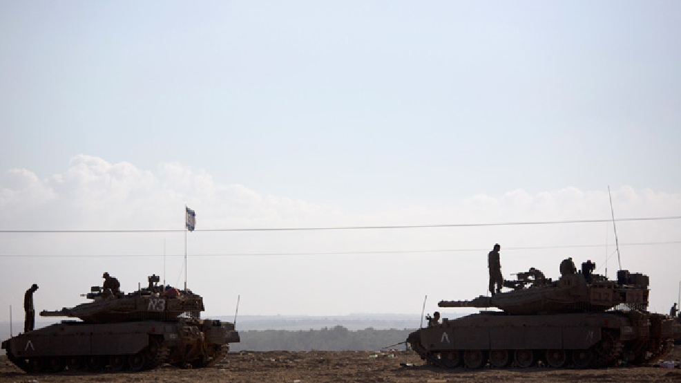 Israeli soldiers work on their tanks near the Israel and Gaza border Friday, July 25, 2014. Early Friday, Israeli warplanes struck tens of houses throughout the Gaza Strip as international efforts continue to broker a cease fire in the 18 day-old war. (AP Photo/Dusan Vranic)