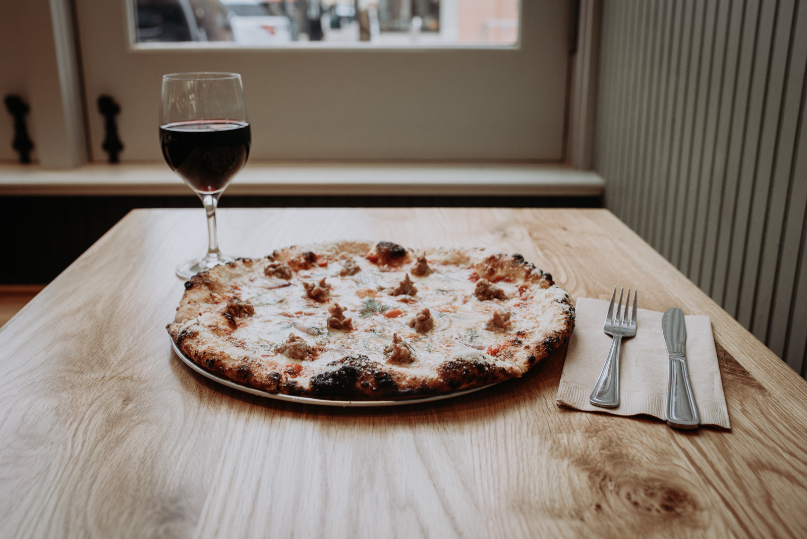Fennel Sausage Pizza: gouda/havarti blend, mozzarella/provolone blend, fennel sausage, tomato sauce red onion, and fennel pollen / Image: Brianna Long // Published: 11.8.17