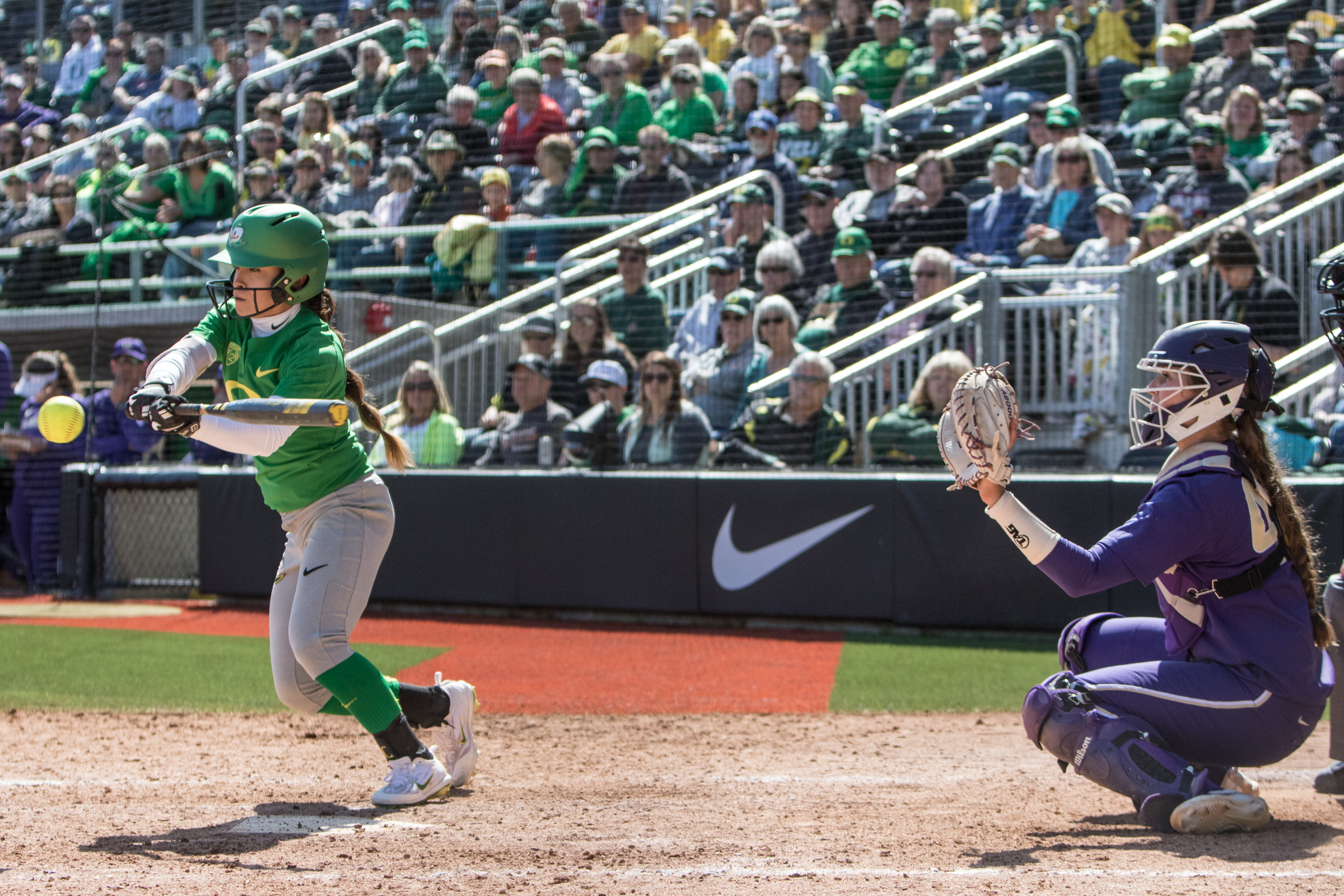 Oregon Ducks outfielder Sammie Puentes (#5) hits the ball along the third base line in the bottom of the ninth inning where a Washington infielder snatched it for the out.  In the final game of a three-game series, the University of Washington Huskies defeated the Oregon Ducks 5-3.  The Ducks led through the bottom of the 7th inning, but Washington's Morganne Flores (#47) tied it up with a two-run double.  Flores drove in two more runs in the 9th to take the lead.  Photo by Austin Hicks, Oregon News Lab