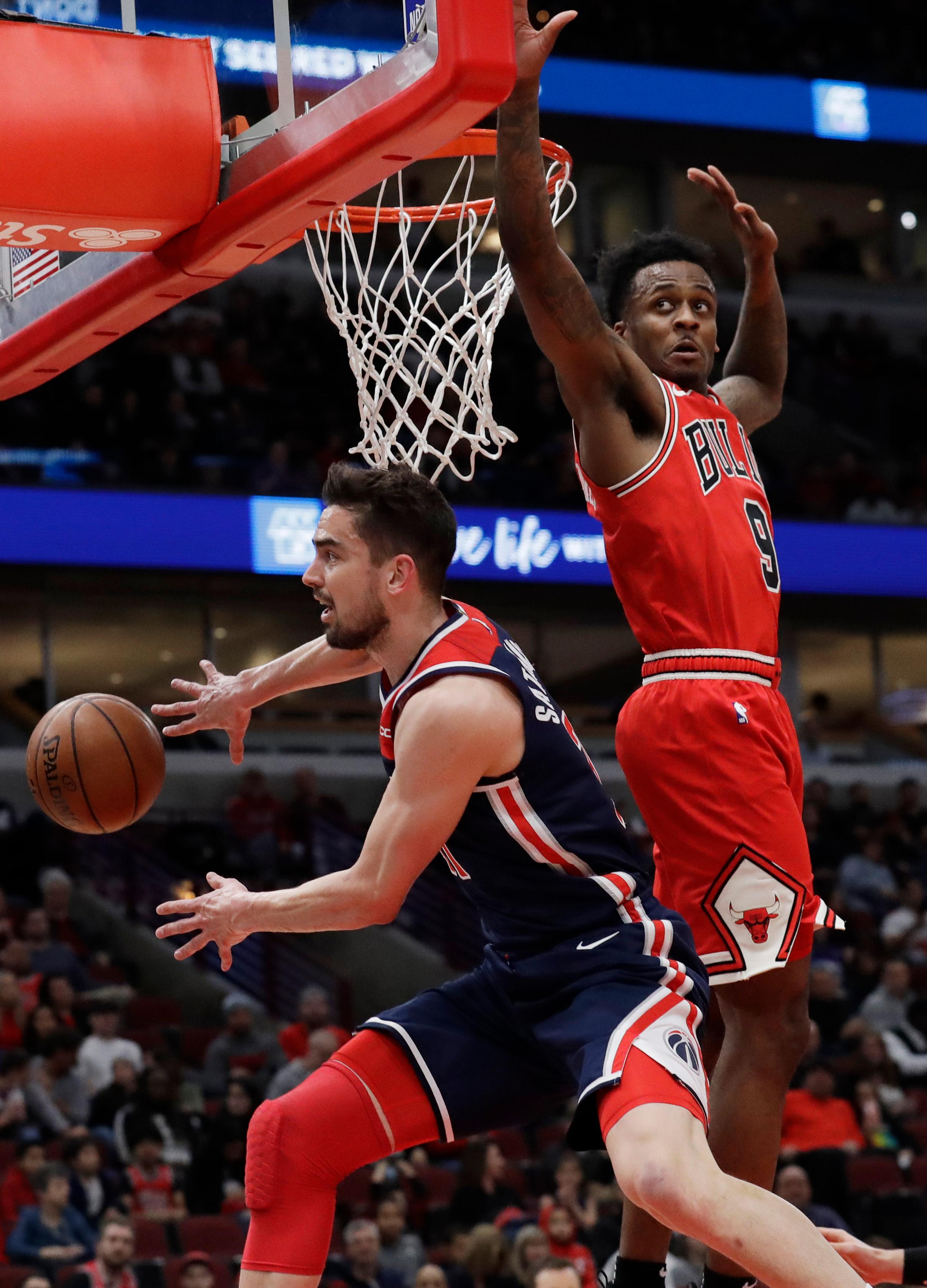 Washington Wizards guard/forward Tomas Satoransky, left, passes the ball as Chicago Bulls guard Antonio Blakeney defends during the first half of an NBA basketball game Wednesday, March 20, 2019, in Chicago. (AP Photo/Nam Y. Huh)