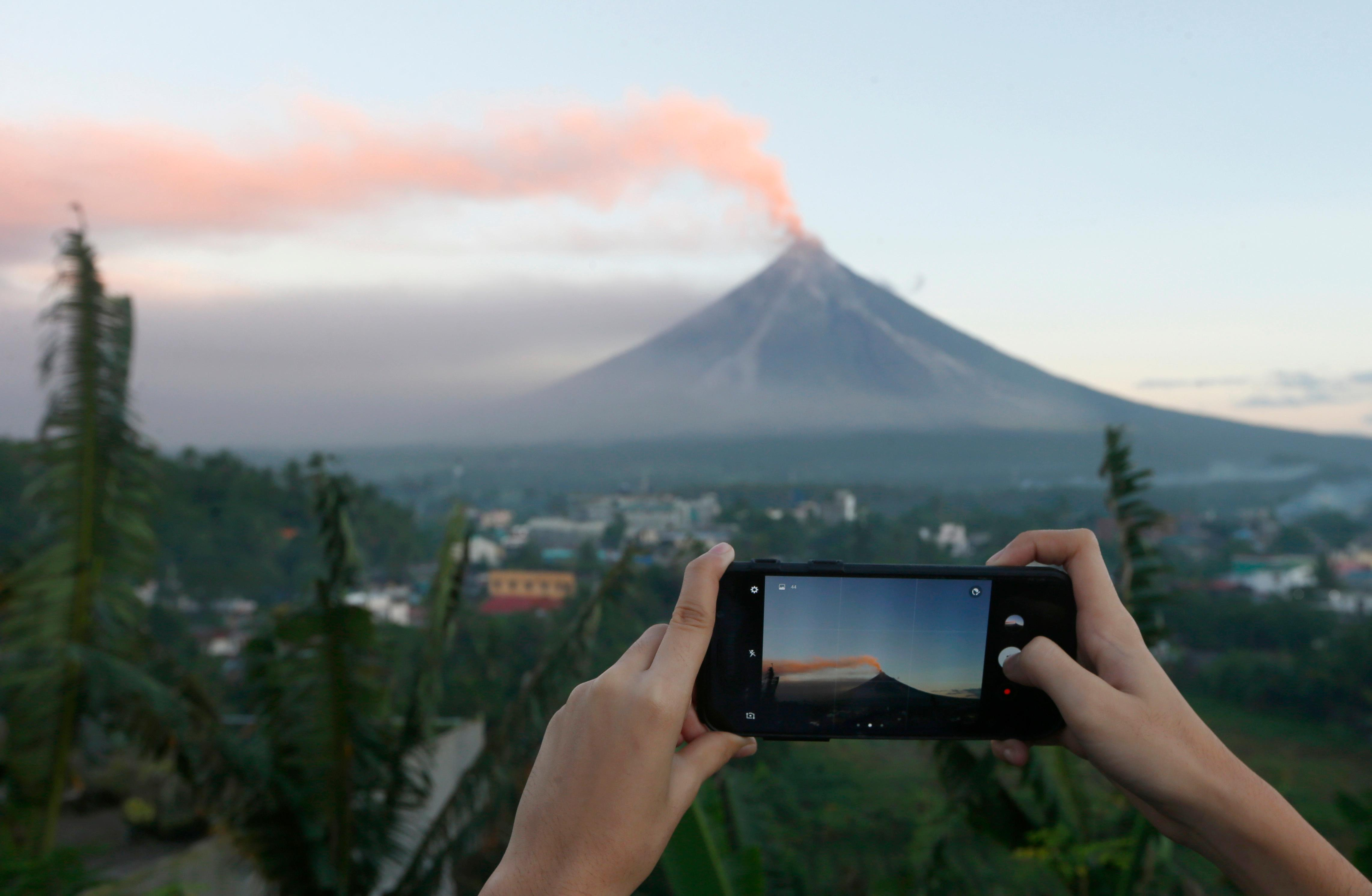 A resident takes photos of Mayon volcano as it spews ash during a lull in its eruption Tuesday, Jan. 23, 2018 as seen from Legazpi city, Albay province, around 340 kilometers (200 miles) southeast of Manila, Philippines. The Philippines' most active volcano ejected a huge column of lava fragments, ash and smoke in another thunderous explosion at dawn Tuesday, sending thousands of villagers back to evacuation centers and prompting a warning that a violent eruption may be imminent. (AP Photo/Bullit Marquez)