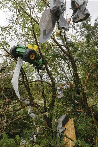 Debris, including a toy tractor, are trapped in a tree following a tornado in Hickman, Neb., Friday.