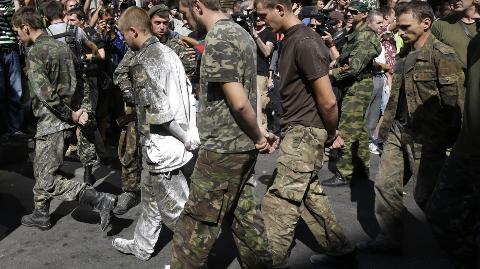 Pro-Russian rebels escort prisoners of war from the Ukrainian army in a central square in Donetsk, eastern Ukraine, Sunday, Aug. 24, 2014. Ukraine has retaken control of much of its eastern territory bordering Russia in the last few weeks, but fierce fighting for the rebel-held cities of Donetsk and Luhansk persists. (AP Photo/Sergei Grits)