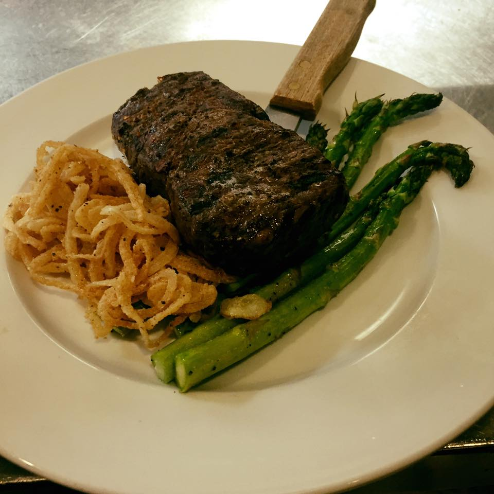 Aged New York Strip: 12 oz. steak paired with onion straws and asparagus / Image provided by Ferrari's Little Italy and Bakery