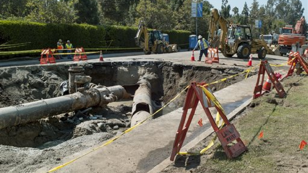 "Los Angeles Department of Water and Power crews work to repair the ""Y"" shaped juncture where a water rupture occurred near the University of California, Los Angeles, involving two main trunk lines on Sunset Boulevard, Thursday, July 31, 2014. Work crews have stopped the last of the water gushing from a 30-inch pipe some 30 hours after it burst. Damage costs have yet to be pegged from the rupture of the pipeline that spewed more than 20 million gallons of water in the midst of California's worst drought in decades. The break in the 93-year-old pipe left a swath of the UCLA campus including its basketball arena swamped with water. (AP Photo/Damian Dovarganes)"