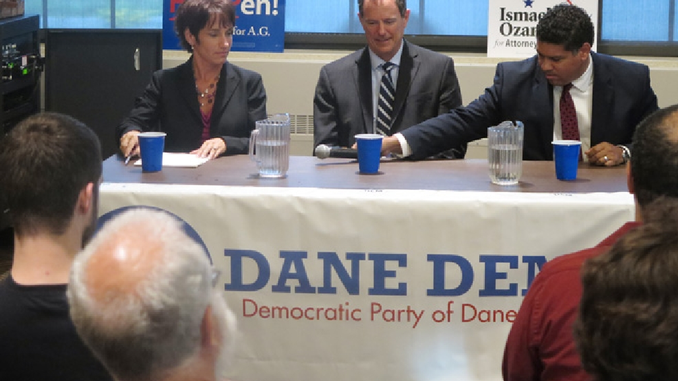 Dane County District Attorney Ismael Ozanne, right, passes a microphone to Jefferson County District Attorney Susan Happ, left, on Tuesday, July 22, 2014, at a forum in Madison for all three Democratic candidates for Wisconsin attorney general, as state Rep. Jon Richards, center, watches. The candidates will square off in a primary Aug. 12. (AP Photo)