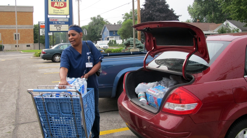Sharon Green loads bottled water into her car she bought after Toledo warned residents not to use its water, Saturday, Aug. 2, 2014 in Toledo, Ohio. About 400,000 people in and around Ohio's fourth-largest city were warned not to drink or use its water after tests revealed the presence of a toxin possibly from algae on Lake Erie. (AP Photo John Seewer)