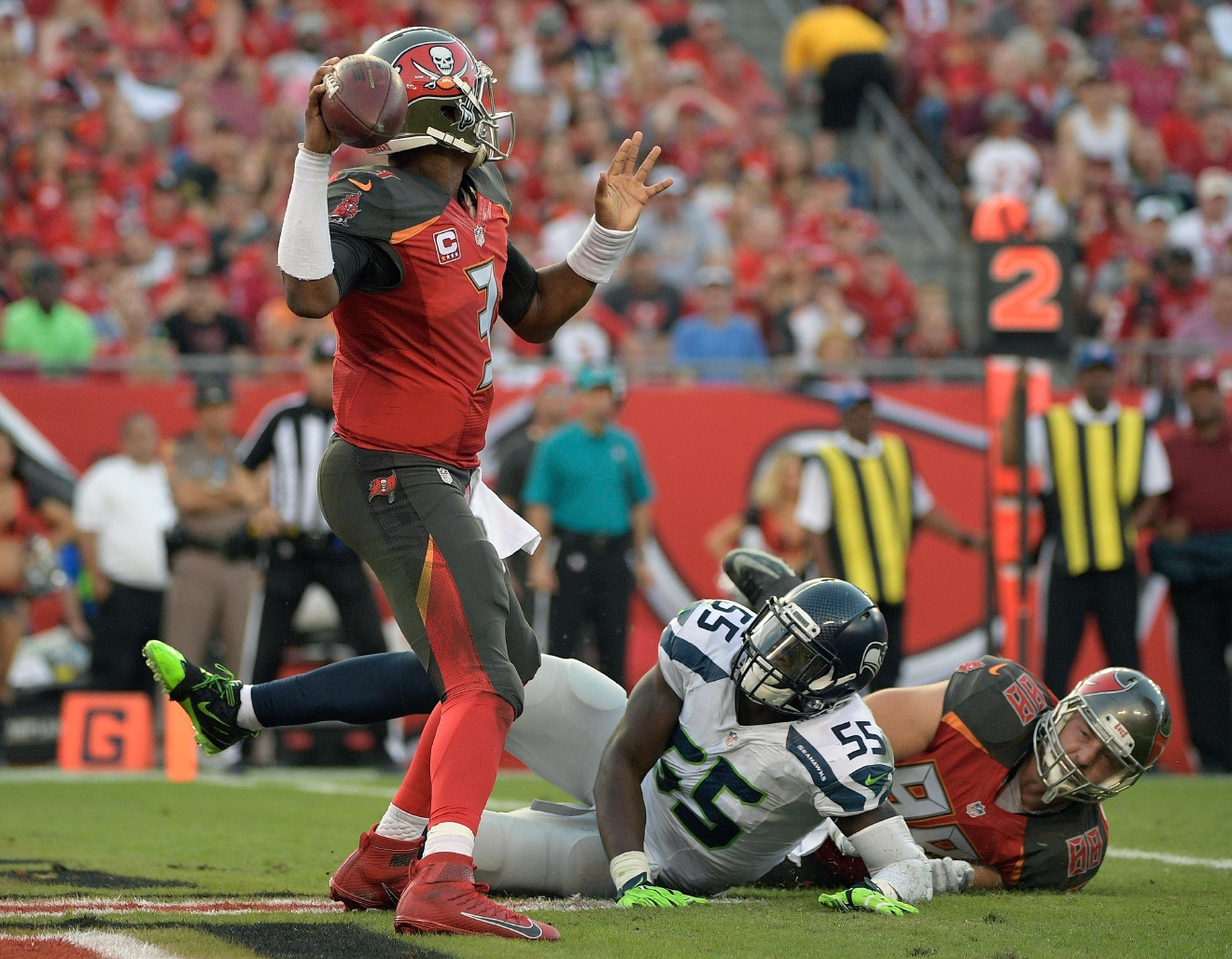Seattle Seahawks defensive end Frank Clark (55) is held by Tampa Bay Buccaneers tight end Luke Stocker (88) as quarterback Jameis Winston (3) throws a pass from the end zone during the second quarter of an NFL football game Sunday, Nov. 27, 2016, in Tampa, Fla. The Seahawks were awarded a safety on the play. (AP Photo/Phelan Ebenhack)