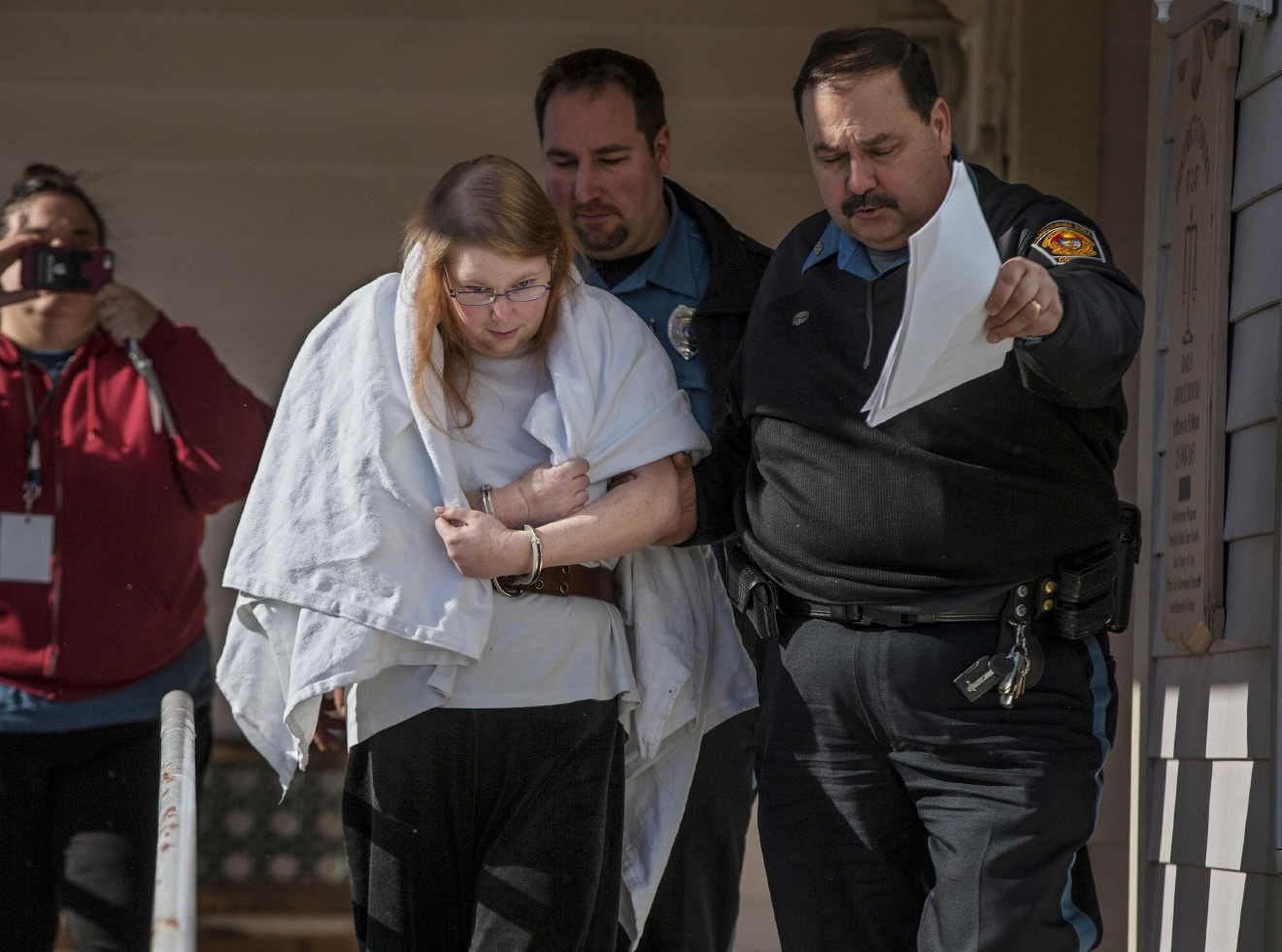 "Sara Packer, center, handcuffed, the adoptive mother of Grace Packer, was led out of District Court in Newtown, Pa., Sunday, Jan. 8, 2017, by Pennsylvania Constables and taken into custody. Packer, whose teenage daughter's dismembered remains were found in the woods last fall, has been charged along with her boyfriend Jacob Sullivan with killing the girl in a ""rape-murder fantasy"" the couple shared, a prosecutor said Sunday. (Michael Bryant/The Philadelphia Inquirer via AP)"