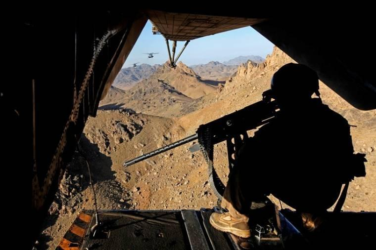 U.S. Marine Corps Gunnery Sgt. Marcus S. McCollum provides aerial security with a GAU-21 .50-caliber machine gun inside a CH-53E Super Stallion helicopter over Helmand province, Afghanistan. McCollum is assigned to Marine Heavy Helicopter Squadron 462.