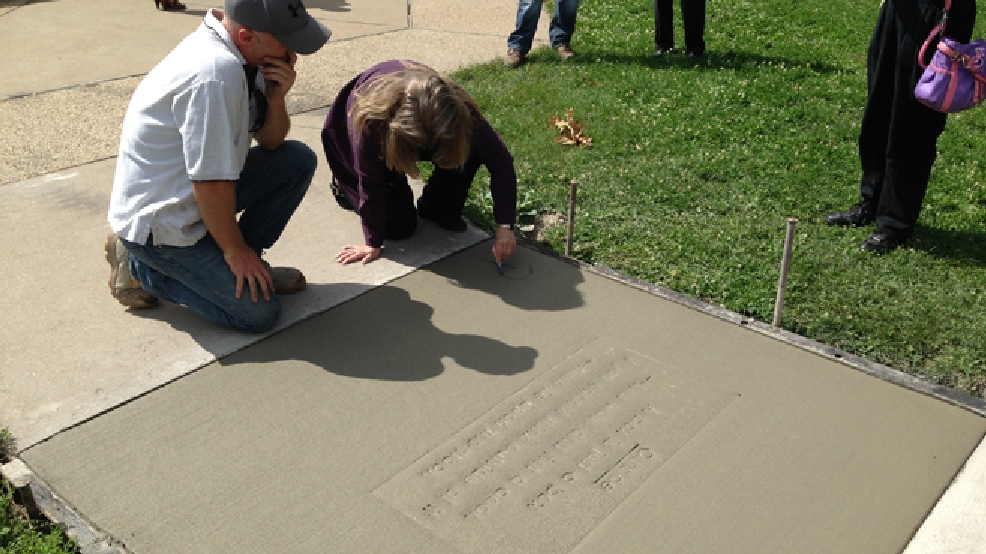 Patricia Casten signs her name to a poem she wrote that was stamped into a sidewalk in Appleton, July 9, 2014. (WLUK/Mike Raasch)