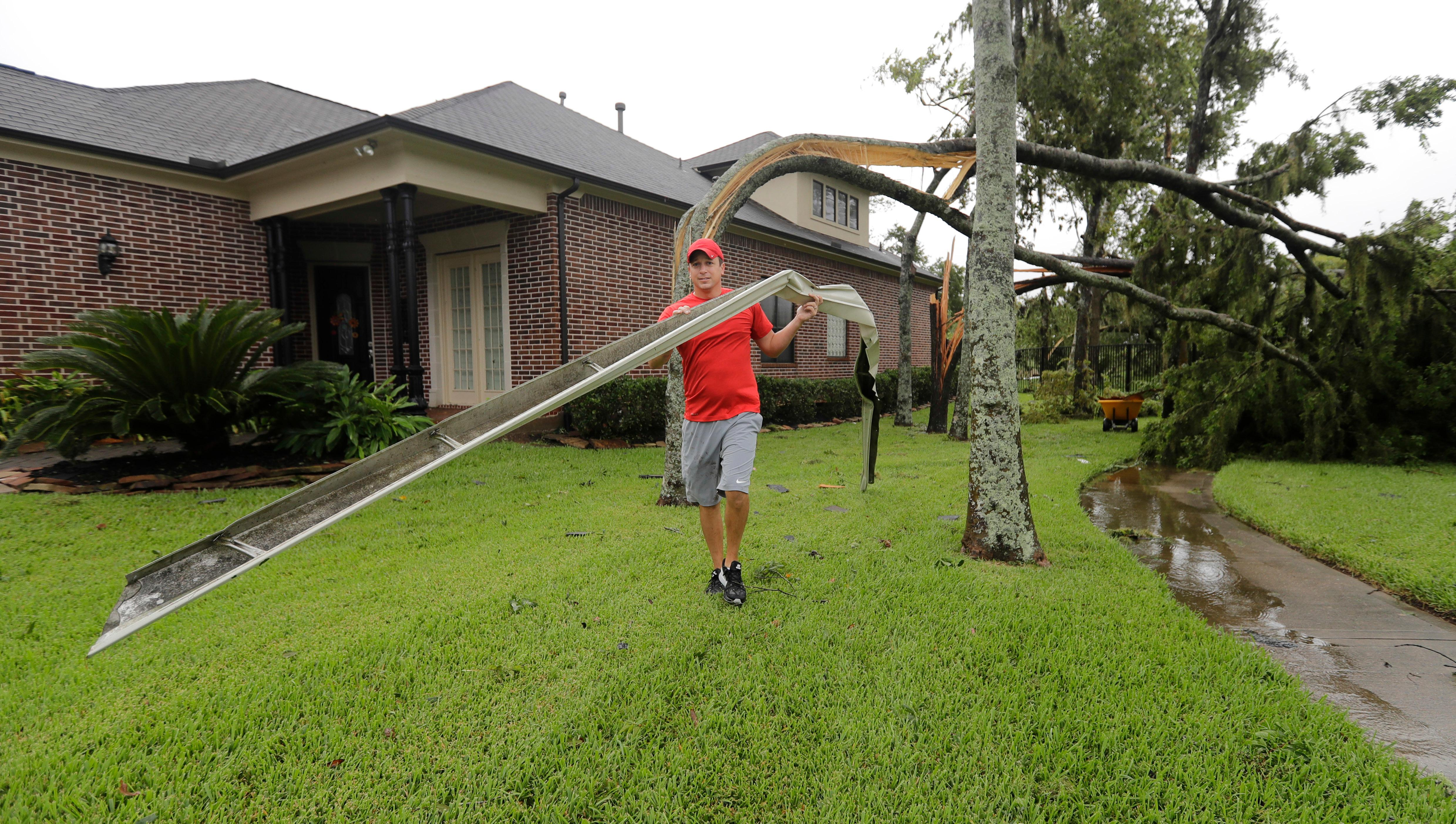 A resident, who wished not to be identified, carries a torn gutter while cleaning up after Hurricane Harvey Saturday, Aug. 26, 2017, in Missouri City, Texas.   Harvey rolled over the Texas Gulf Coast on Saturday, smashing homes and businesses and lashing the shore with wind and rain so intense that drivers were forced off the road because they could not see in front of them. (AP Photo/David J. Phillip)