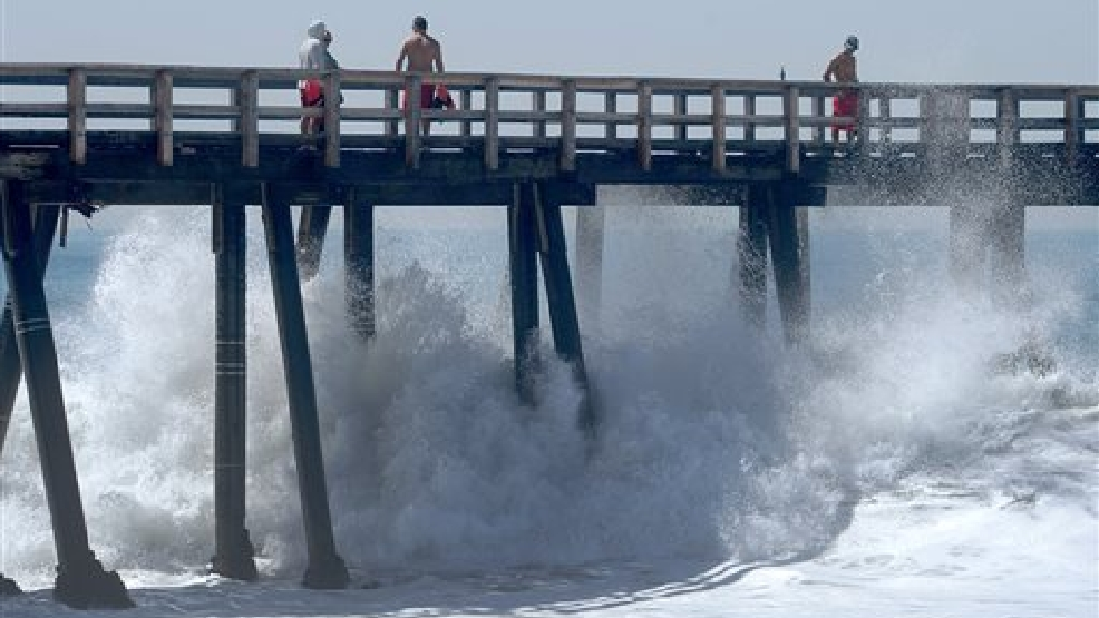 Lifeguards check on two surfers as waves pound the Hueneme beach pier in Port Hueneme, Calif., Wednesday, Aug. 27, 2014. Thundering surf spawned by a Pacific hurricane pounded the Southern California coast Wednesday, causing minor flooding in a low-lying beach town, knocking pilings from under the Malibu Pier and drawing daredevil surfers and body-boarders into churning waves as crowds of spectators lined the shore. (AP Photo/Ventura County Star, Rob Varela)