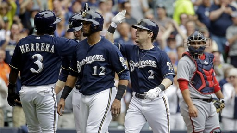 Washington Nationals catcher Sandy Leon watches as Milwaukee Brewers' Scooter Gennett (2)  is congratulated at home by Elian Herrera (3) after hitting a grand slam during the second inning of a baseball game Wednesday, June 25, 2014, in Milwaukee. (AP Photo/Morry Gash)