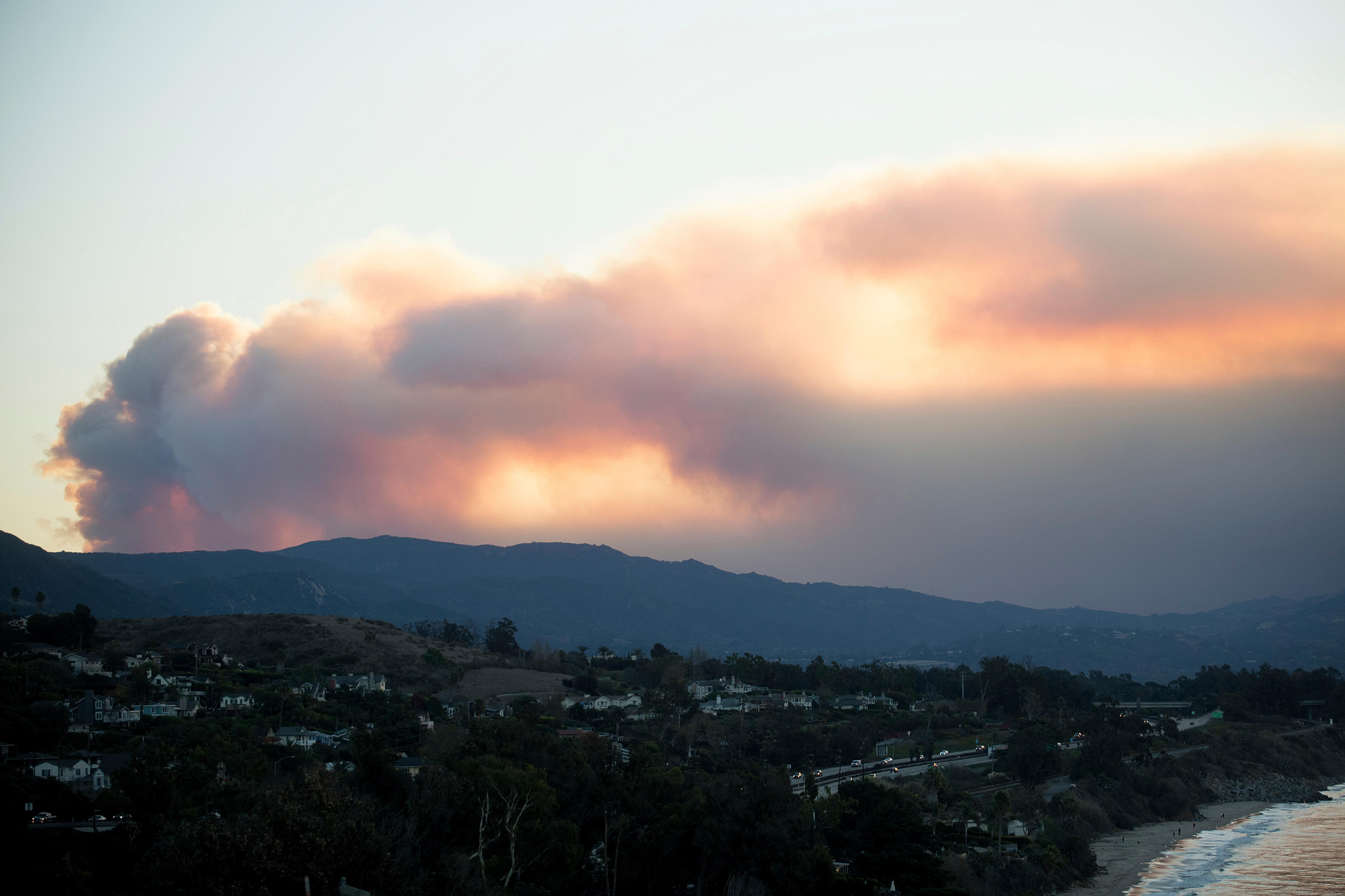 Seen from Carpinteria, Calif., smoke from a wildfire billows over Ventura, on Tuesday, Dec. 5, 2017. (AP Photo/Noah Berger)