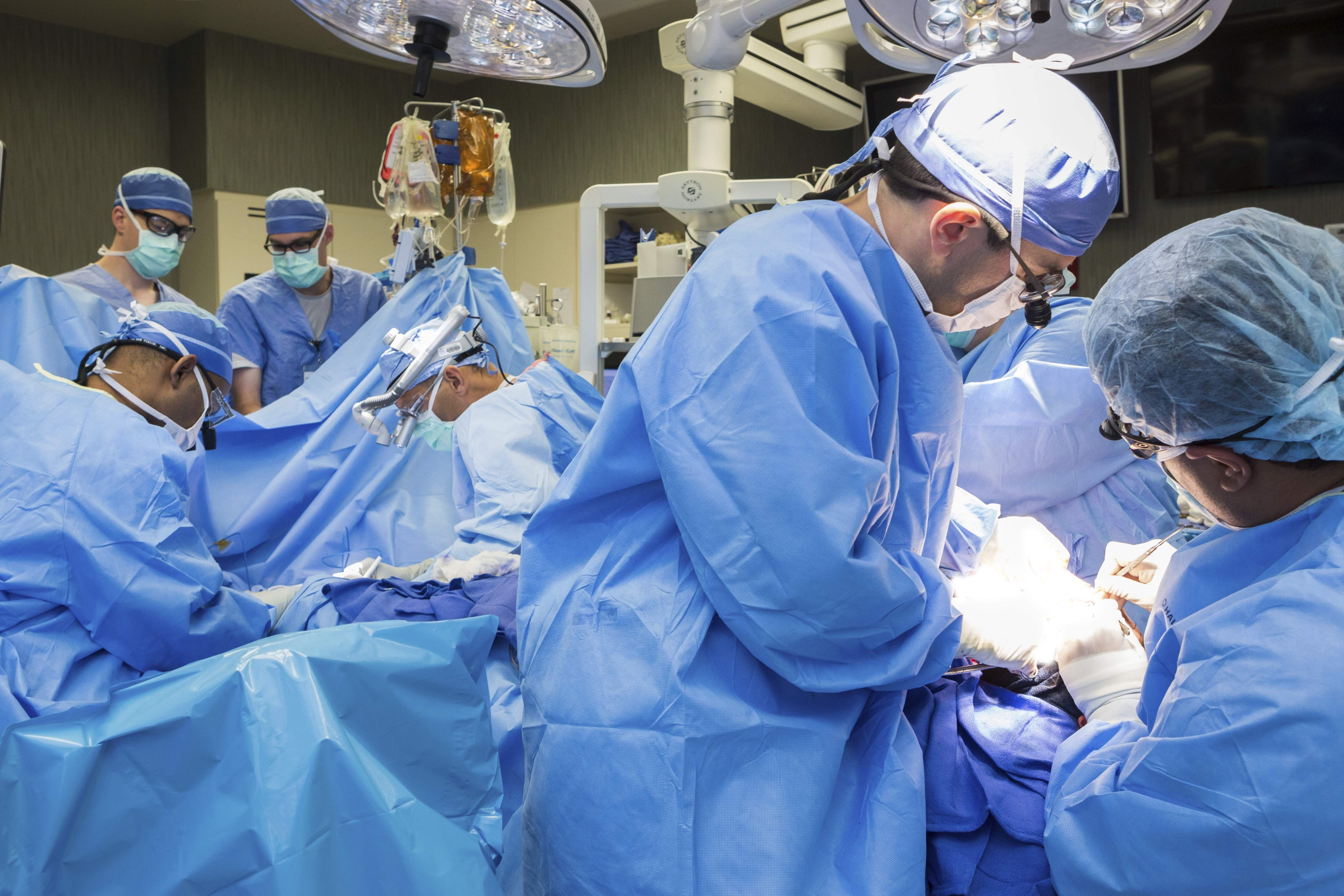 In this June 11, 2016, photo provided by the Mayo Clinic, a medical team performs a face transplant surgery at the medical center in Rochester, Minn. The surgery that started shortly before midnight Friday was over early Monday morning. THE ASSOCIATED PRESS