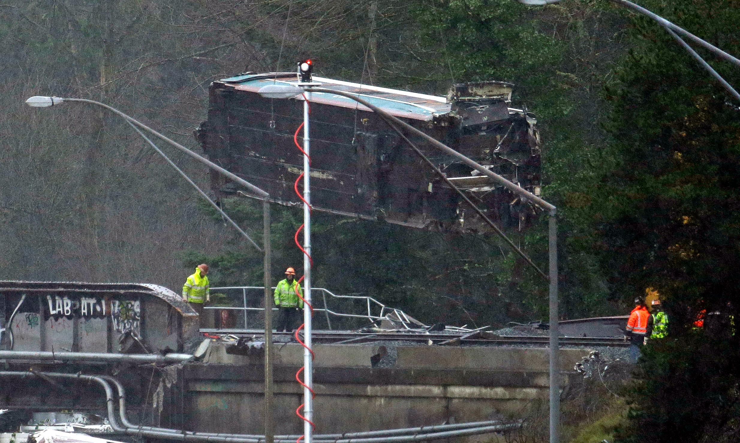 A damaged Amtrak train car is lowered from an overpass at the scene of a train crash onto Interstate 5 a day earlier, Tuesday, Dec. 19, 2017, in DuPont, Wash. Federal investigators say they don't yet know why the Amtrak train was traveling 50 mph over the speed limit when it derailed Monday south of Seattle.  (AP Photo/Elaine Thompson)