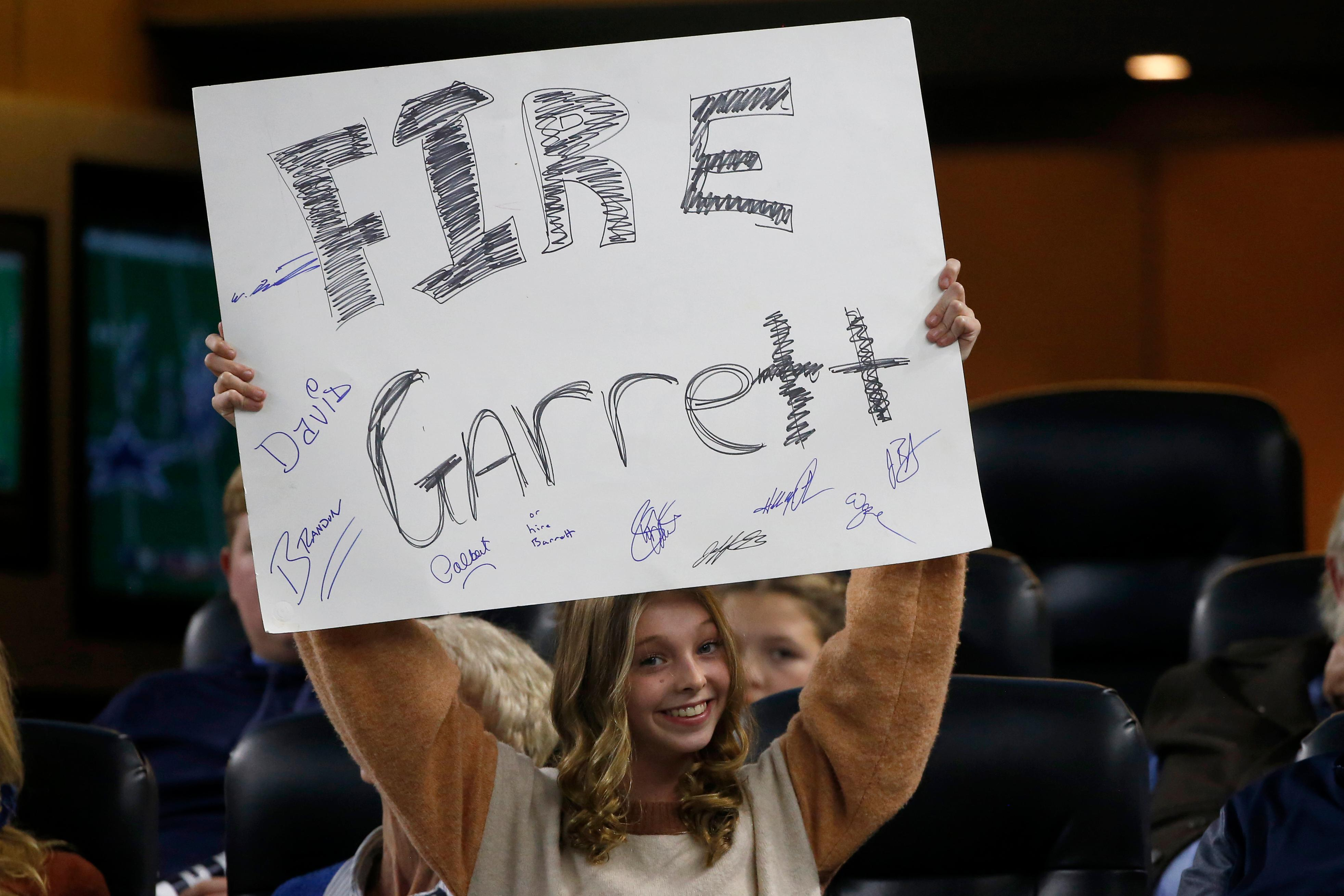A young fan holds a sign calling for the firing of Dallas Cowboys head coach Jason Garrett in the second half of an NFL football game against the Buffalo Bills in Arlington, Texas, Thursday, Nov. 28, 2019. (AP Photo/Ron Jenkins)