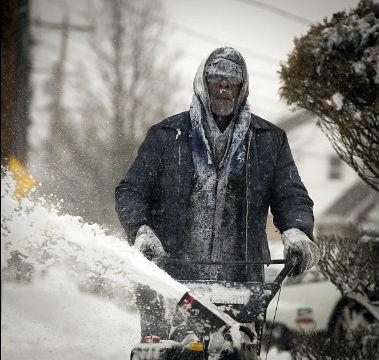 Snow clings to the clothing and facial hair of Jerome Williams as he uses a snowblower in front of his home in Roosevelt, New York, on January 3.