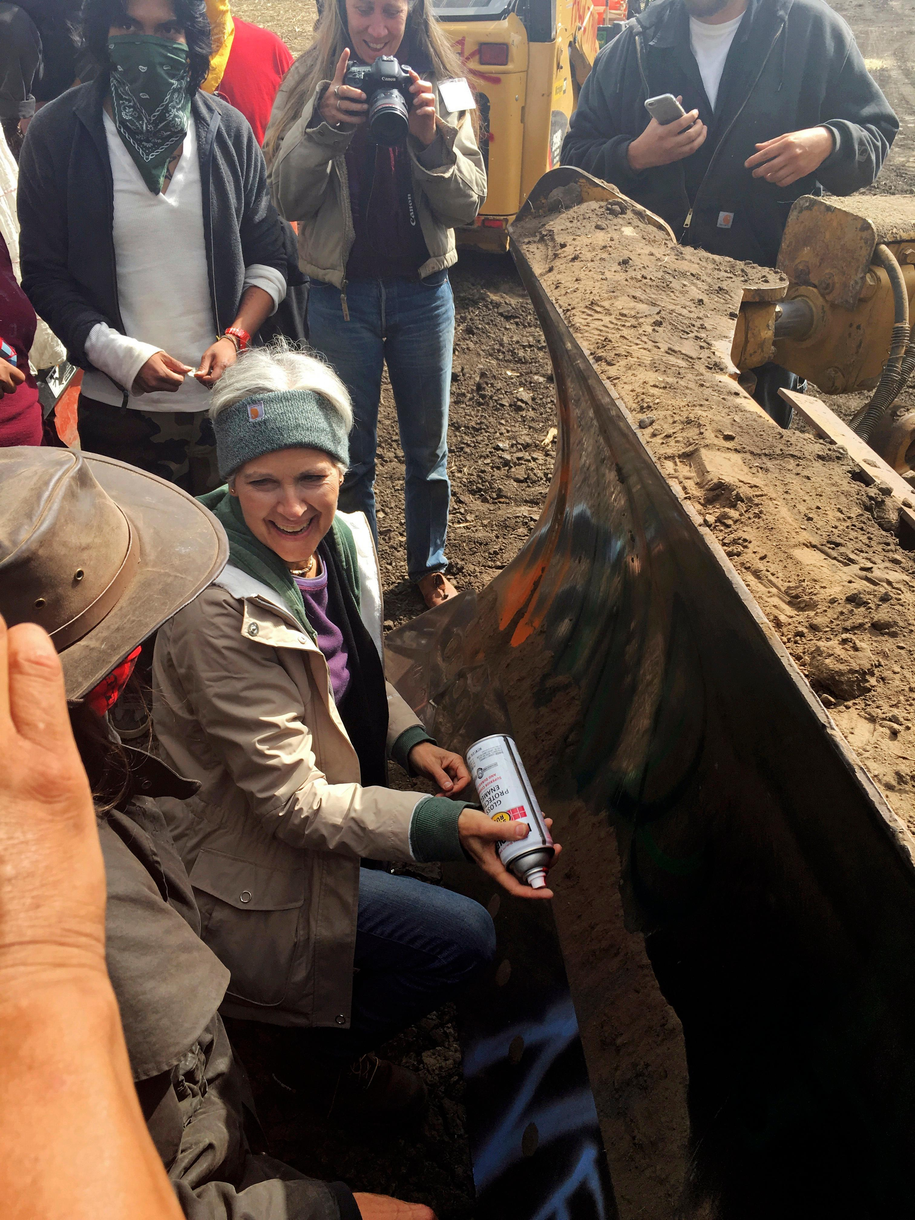 "FILE - In this Sept. 6, 2016, file photo, Green Party presidential candidate Jill Stein prepares to spray-paint ""I approve this message"" in red paint on the blade of a bulldozer at a protest against the Dakota Access Pipeline in the area of Morton County, N.D. Stein has reached a plea agreement with prosecutors to resolve criminal charges filed against her in North Dakota nearly a year ago for protesting the Dakota Access oil pipeline, court records show. (Alicia Ewen/KX News via AP, File)"