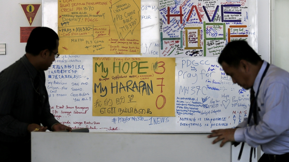 Airport staff move a white board plastered with messages of hope and encouragement to all involved with the missing Malaysia Airlines jet, MH370, at the Kuala Lumpur International Airport, Tuesday, March 11, 2014, in Sepang, Malaysia. Authorities hunting for the missing Malaysia Airlines jetliner expanded their search on land and sea Tuesday, reflecting the difficulties in locating traces of the plane more than three days after it vanished. (AP Photo/Wong Maye-E)
