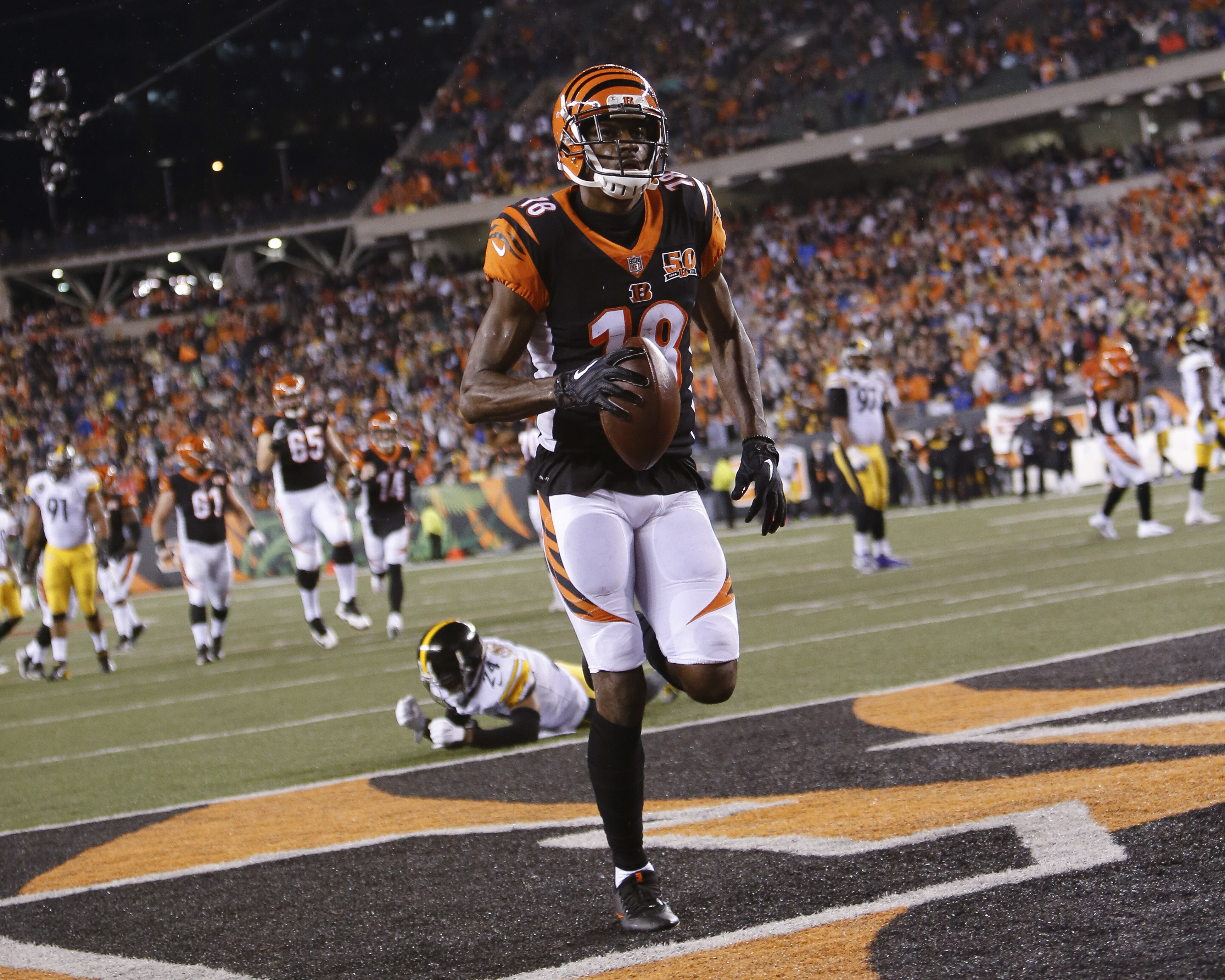 Cincinnati Bengals wide receiver A.J. Green (18) runs in a touchdown against Pittsburgh Steelers cornerback Coty Sensabaugh (24) in the first half of an NFL football game, Monday, Dec. 4, 2017, in Cincinnati. (AP Photo/Frank Victores)