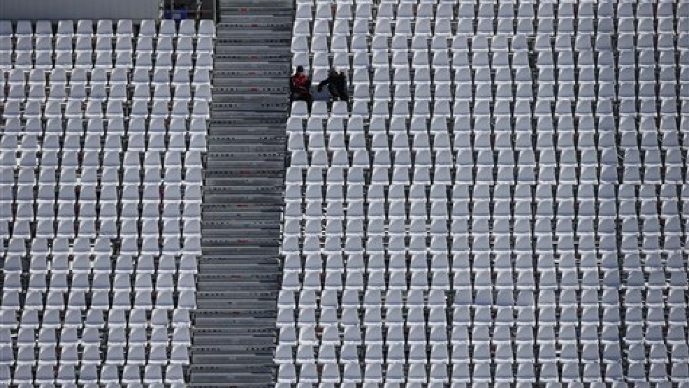 Workers sit in spectator seats during a ski slopestyle training session at the Rosa Khutor Extreme Park, days before the opening of the 2014 Winter Olympics, Tuesday, Feb. 4, 2014, in Krasnaya Polyana, Russia. (AP Photo/Andy Wong)