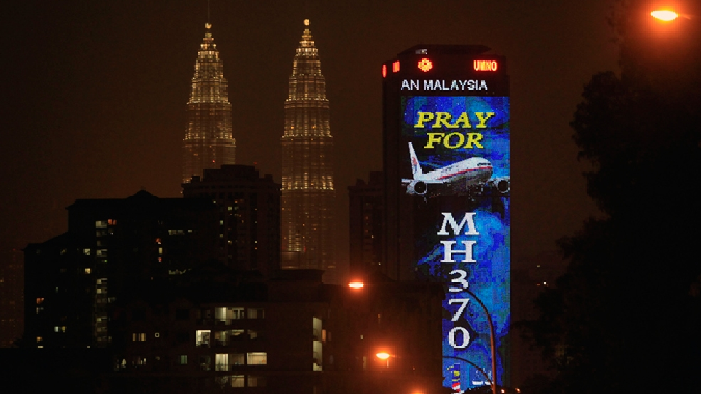 "An office building is illuminated with LED lights displaying ""Pray for MH370"" next to Malaysia's landmark Petronas Twin Towers in Kuala Lumpur, Malaysia, Wednesday, March 19, 2014. Investigators are trying to restore files deleted last month from the home flight simulator of the pilot aboard the missing Malaysian plane to see if they shed any light on the disappearance, Malaysia's defense minister said Wednesday. (AP Photo/Lai Seng Sin)"