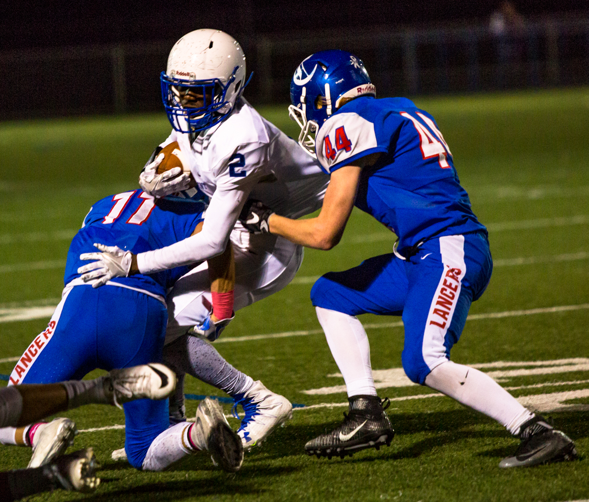 Churchill Lancers safety Lucas Schwin (#11) and line backer Cody Coker (#44) tackle Eagle Point Eagles running back Bennet Rodgers (#2).  Eagle Point defeated Churchill 42-35. Photo by Justin Hartney, Oregon News Lab