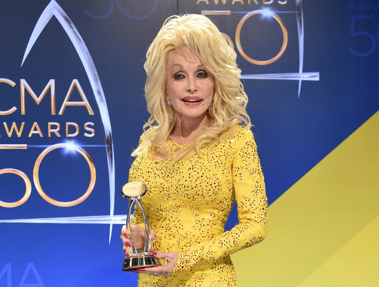 FILE - In this Nov. 2, 2016 file photo, Dolly Parton poses in the press room with the Willie Nelson Lifetime Achievement Award during the 50th annual CMA Awards in Nashville, Tenn. Parton says she's heartbroken about wildfires that tore through the Tennessee county where she grew up, but spared the Dollywood theme park that bears her name. At least 14,000 people have been forced to evacuate the tourist area of Gatlinburg, Tennessee, and a dozen people have been injured in the wildfires. (Photo by Evan Agostini/Invision/AP, File)
