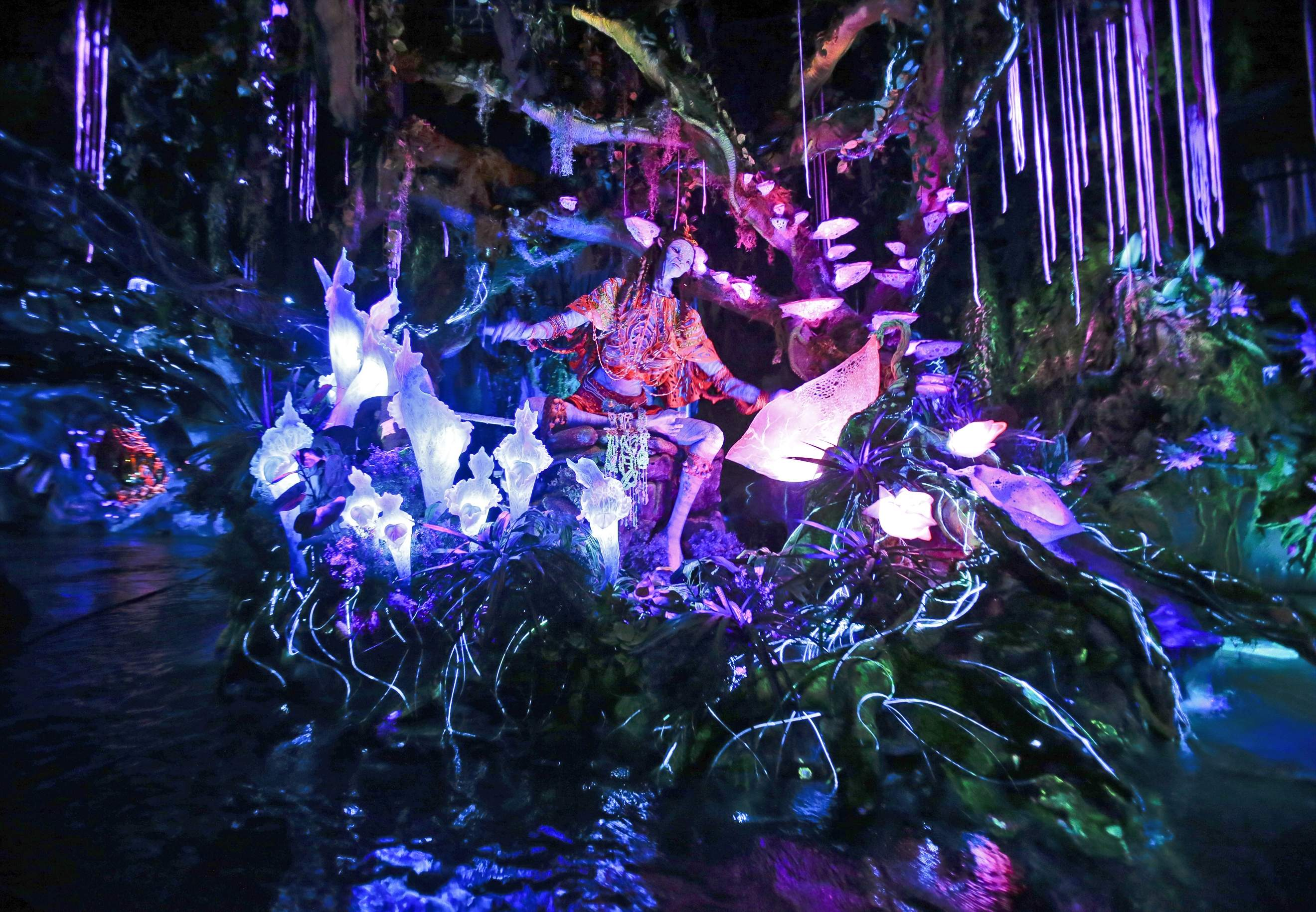 In this Saturday, April 29, 2017, photo, the Na'vi Shaman of Songs celebrates with music in Na'vi River Journey ride at Pandora-World of Avatar land attraction in Disney's Animal Kingdom theme park at Walt Disney World in Lake Buena Vista, Fla. The 12-acre land, inspired by the 'Avatar' movie, opens in Florida at the end of May at Walt Disney World's Animal Kingdom. It cost a half-billion dollars. THE ASSOCIATED PRESS