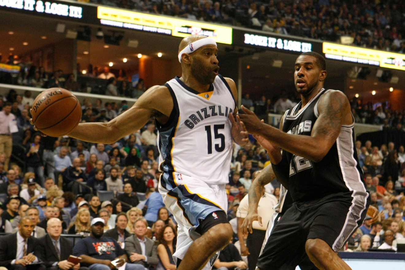 Memphis Grizzlies' Vince Carter (15) passes while being defended by San Antonio Spurs' LaMarcus Aldridge (12) in the first half of an NBA basketball game Saturday, March 18, 2017, in Memphis, Tenn. (AP Photo/Karen Pulfer Focht)