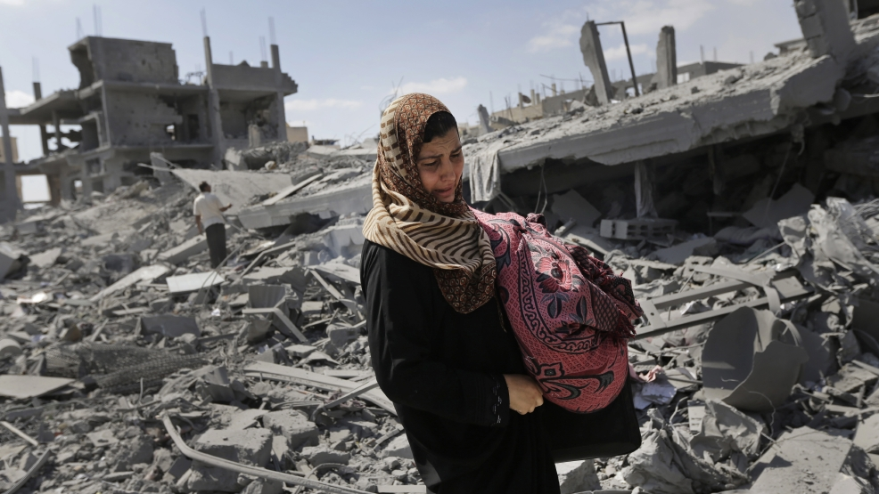 A Palestinian woman carries her belongings past the rubble of houses destroyed by Israeli strikes in Beit Hanoun, northern Gaza Strip, Saturday, July 26, 2014. Thousands of Gaza residents who had fled Israel-Hamas fighting streamed back to devastated border areas during a lull Saturday, and were met by large-scale destruction: scores of homes were pulverized, wreckage blocked roads and power cables dangled in the streets. (AP Photo/Lefteris Pitarakis)